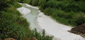 VIDEO USG și Oltchim POLUEAZĂ pârâul Govora, legea le permite, dar plătesc miliarde…